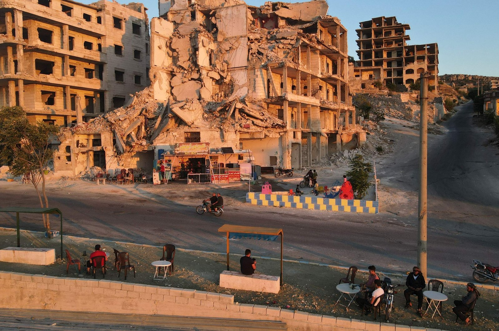 People sit in front of Abu Ali's cafe, set up on the ground floor of a building heavily damaged during the civil war, in the of Ariha in the opposition-held northwestern Idlib province, Syria, July 11, 2021. (Photo by Aaref Watad/AFP)