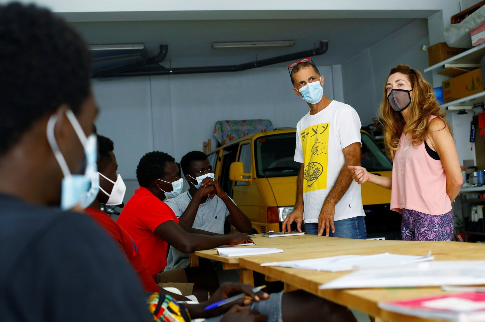 Isabel Florido (R) and Tito Martin teach Spanish classes to a group of Senegalese migrants who arrived on the island by boat, in Las Palmas, on the island of Gran Canaria, Spain, July 21, 2021. (Reuters Photo)
