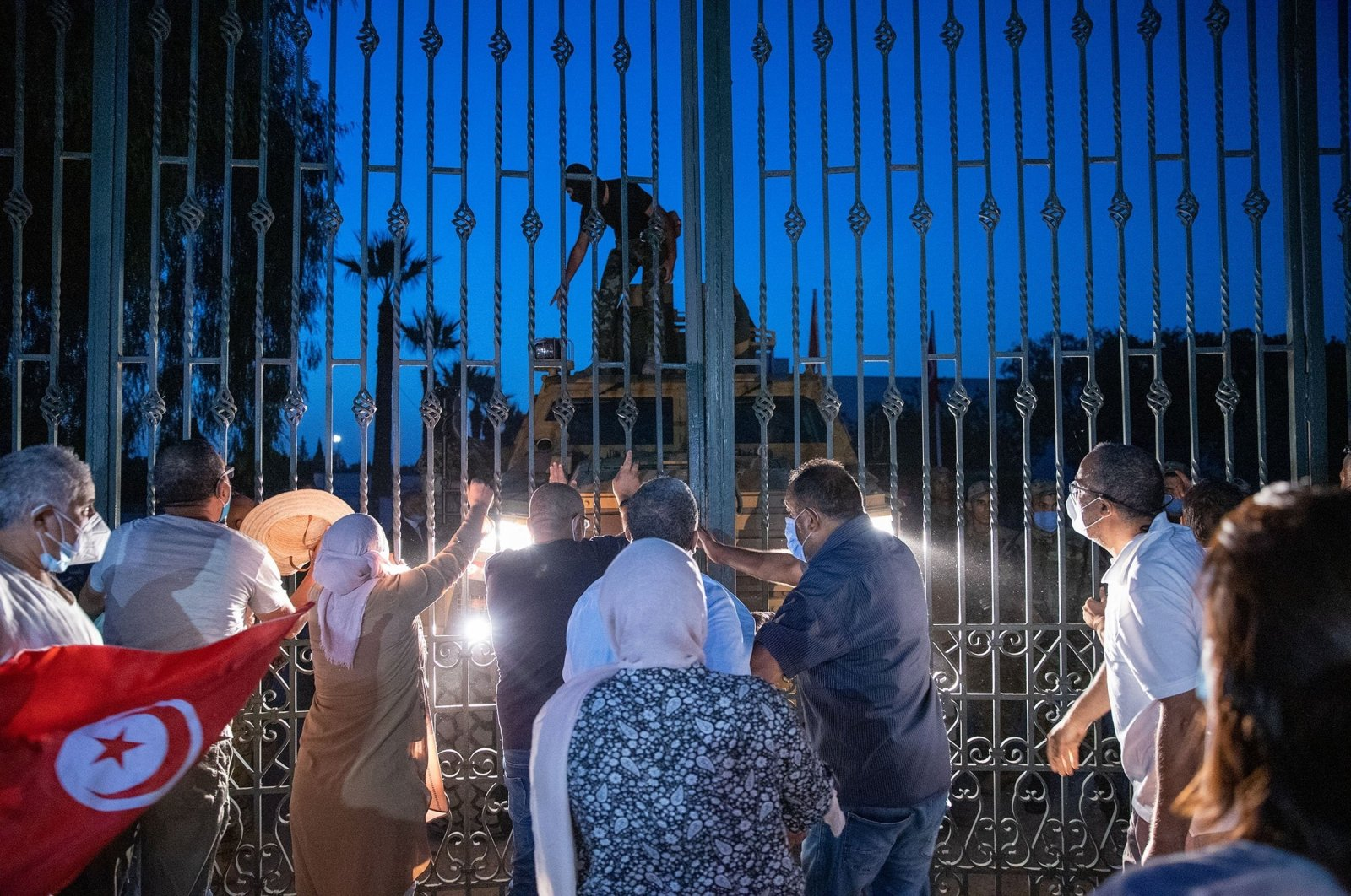 Supporters of the Ennahdha party stand at the gates of the parliament, protesting the drastic political move as a coup, July 26, 2021. (AA Photo)