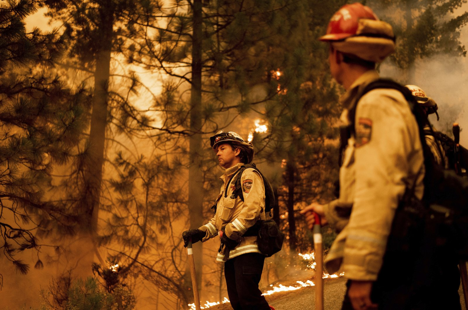 Firefighter Jason Prado monitors flames as his crew burns vegetation to stop the Dixie Fire from spreading near Prattville in Plumas County, California, U.S., July 23, 2021. (AP Photo)