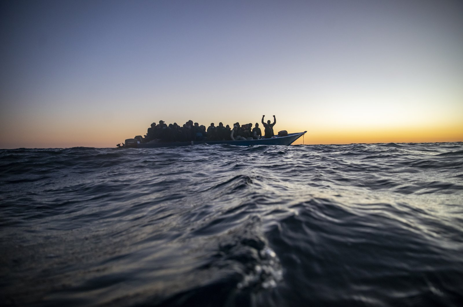 In this Feb. 12, 2021 file photo, migrants and refugees from various countries wait for assistance aboard an overcrowded wooden boat, as aid workers of the Spanish NGO Open Arms approach them in the Mediterranean Sea, international waters, at 122 miles off the Libyan coast. (AP Photo)