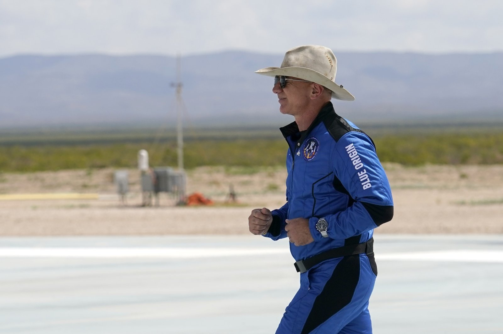 Jeff Bezos, the founder of Amazon and space tourism company Blue Origin, jogs onto Blue Origin's New Shepard rocket landing pad to pose for photos at the spaceport near Van Horn, Texas, on July 20, 2021. (AP Photo)