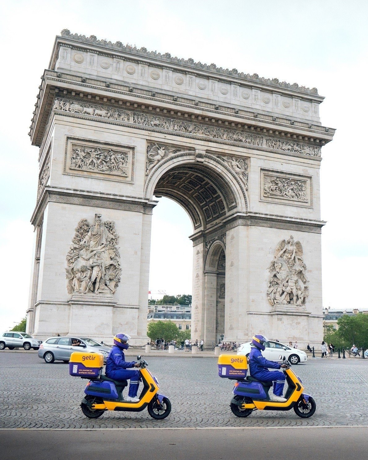 Getir couriers pass by the Arc de Triomphe on Champs Elysees avenue in Paris, France, June 22, 2021. (IHA Photo)