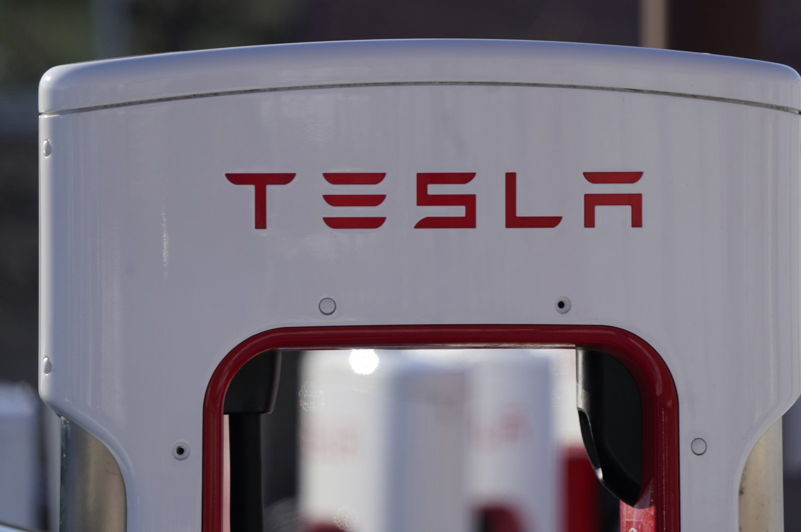 The company logo is shown at the top of a supercharger for Tesla automobiles near shops Feb. 25, 2021 in Boulder, Colo. (AP Photo)
