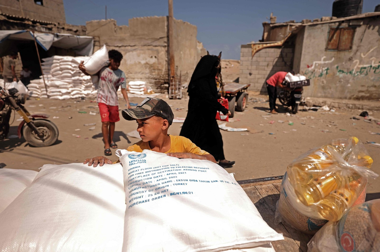 Palestinians collect food aid at a distribution center run by United Nations Relief and Works Agency (UNRWA), in Gaza City on July 26, 2021. (AFP Photo)