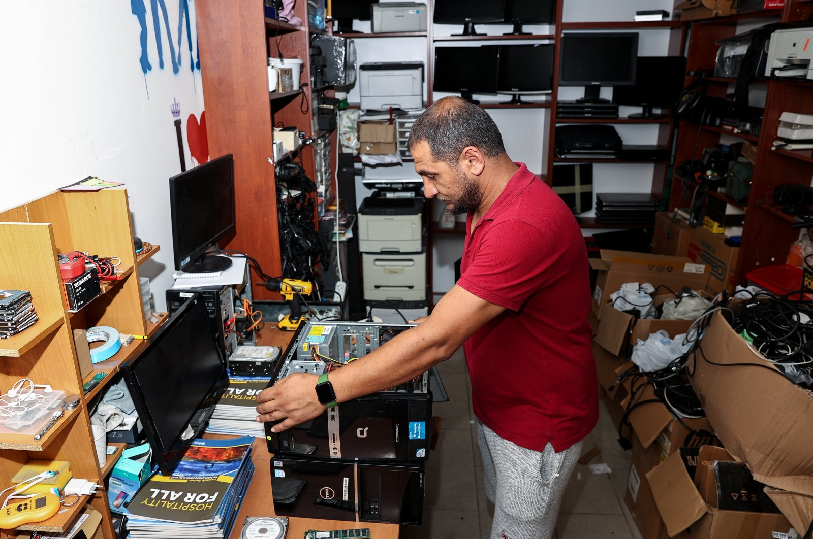 A worker fixes old computers donated to the social startup, in Istanbul, Turkey, July 27, 2021. (AA PHOTO)
