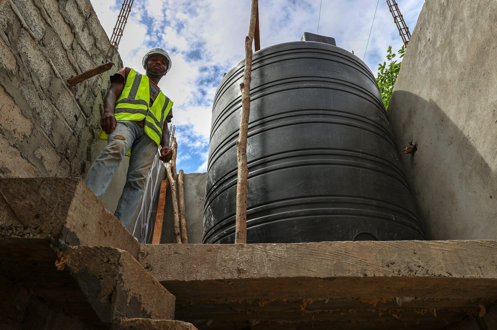 A worker stands next to a tank placed atop a water well under construction, in Boke, Guinea, July 27, 2021. (AA PHOTO)