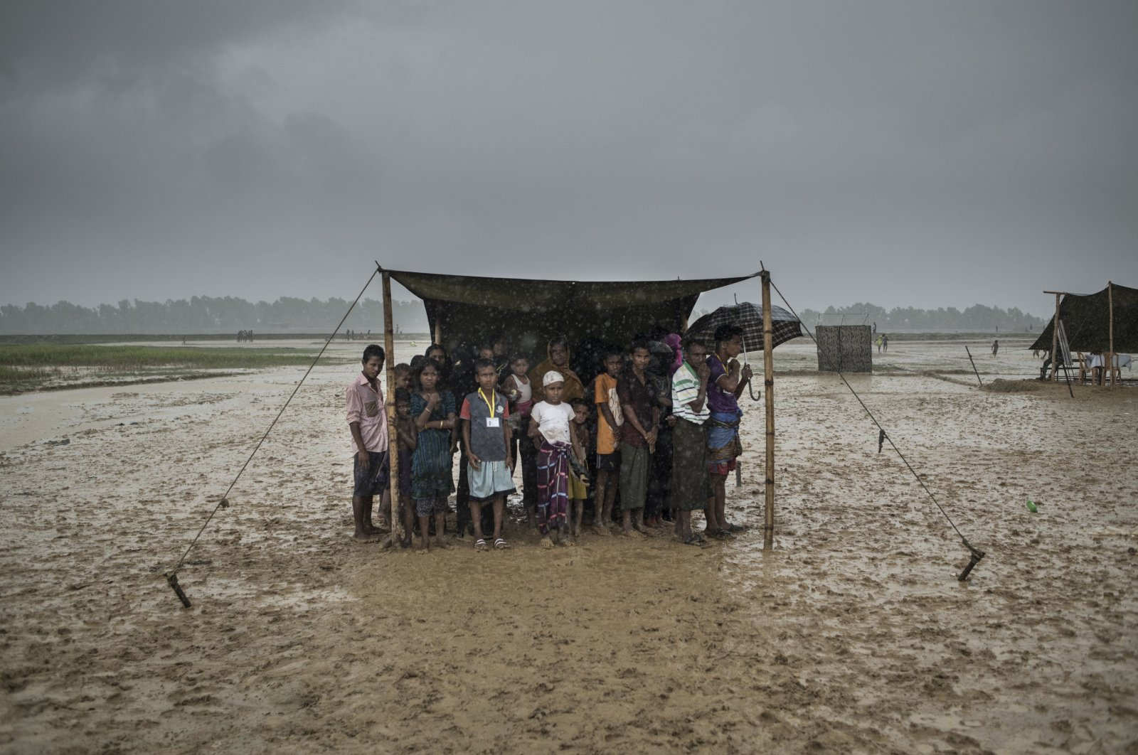 Rohingya Muslim refugees take shelter from the rain during a food distribution at Nayapara refugee camp in Bangladesh's Ukhia district on October 6, 2017. (AFP Photo)