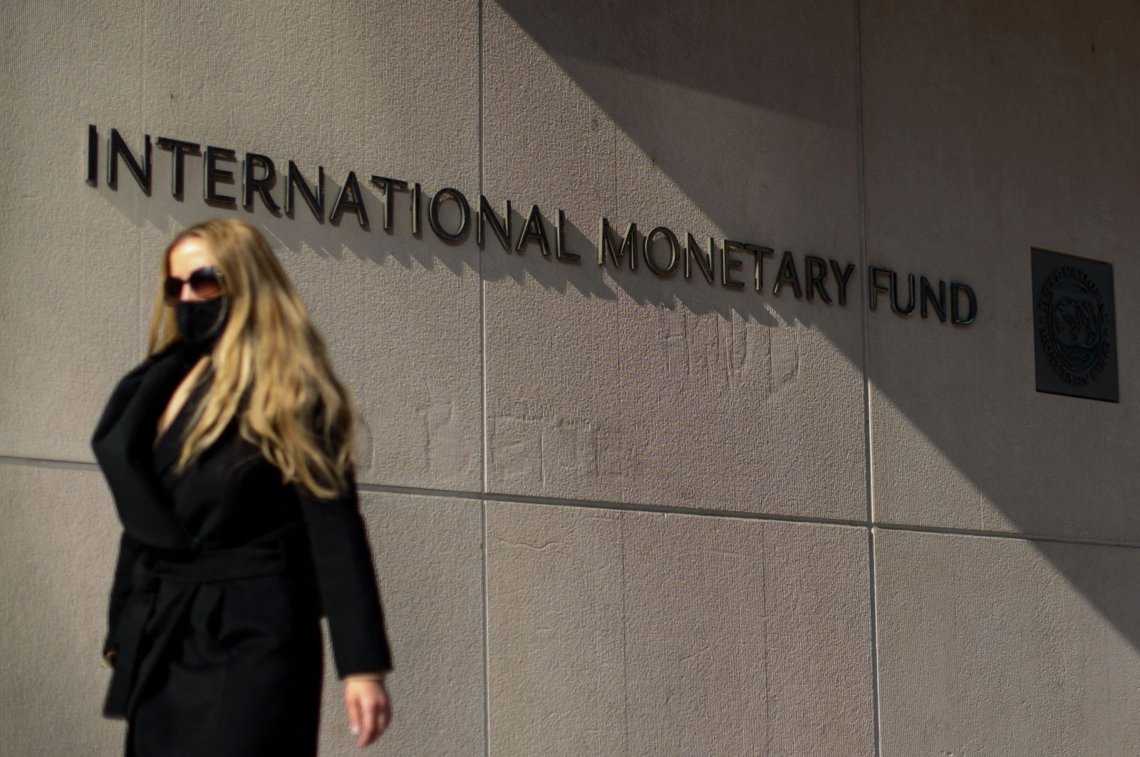 A woman walks past the International Monetary Fund (IMF) headquarters building in Washington, D.C., U.S., April 5, 2021. (AFP Photo)