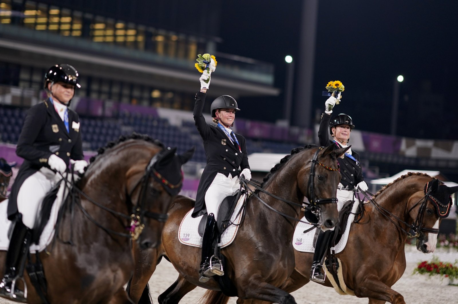 Germany's Dorothee Schneider, from left, Jessica von Bredow-Werndl and Isabell Werth take a victory lap after receiving the gold medal for the equestrian dressage team event at the 2020 Summer Olympics, Tuesday, July 27, 2021, in Tokyo. (AP Photo/David Goldman)