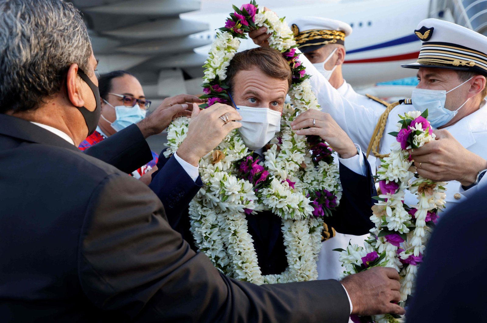 France's President Emmanuel Macron (C) is wrapped in garlands upon his arrival at Faa'a international airport for a visit to Tahiti in French Polynesia on July 24, 2021. (AFP Photo)