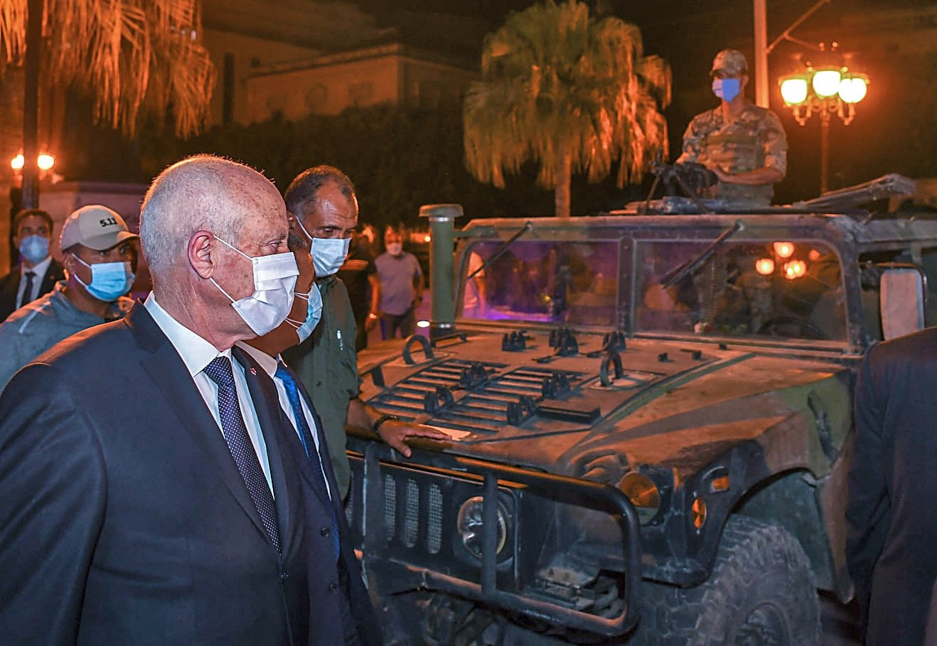 Tunisian President Kais Saied walking past a military vehicle in Tunis's central Habib Bourguiba Avenue, after he ousted the prime minister and ordered the parliament closed for 30 days, in the capital Tunis, Tunisia, on July 26, 2021. (AFP Photo)