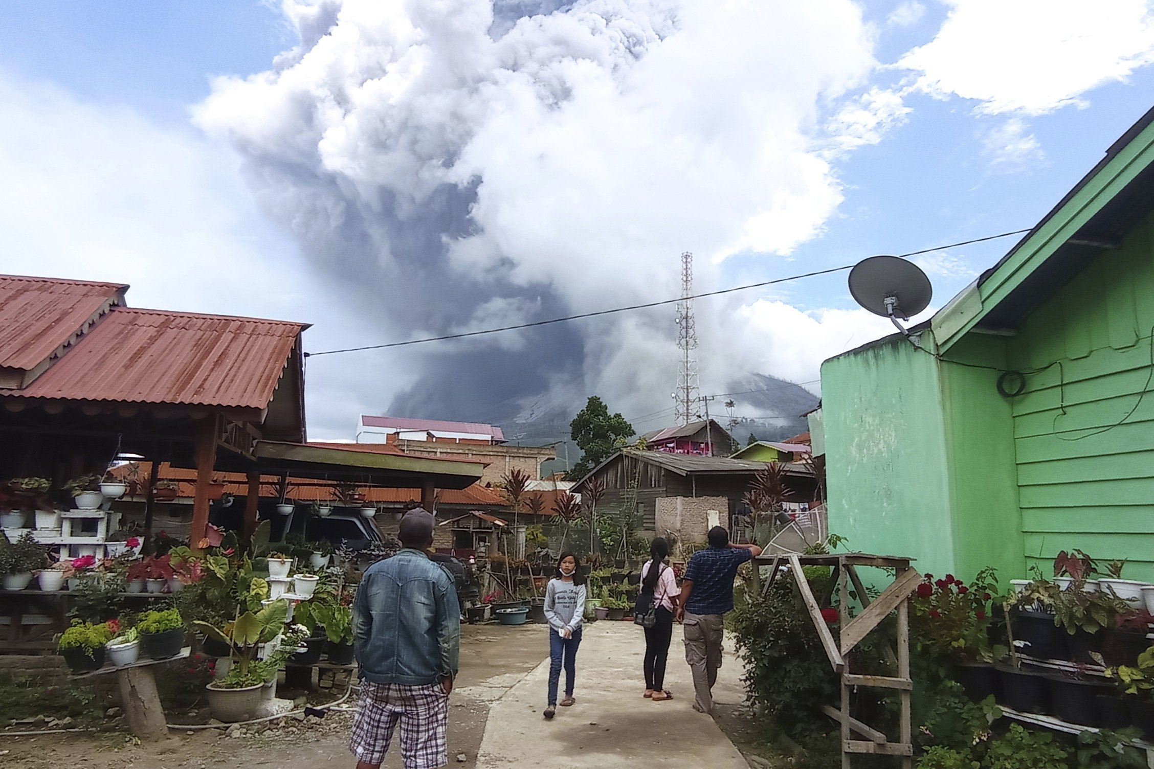 People watch as Mount Sinabung spews volcanic materials during an eruption in Karo, North Sumatra, Indonesia, July 28, 2021. (AP Photo)