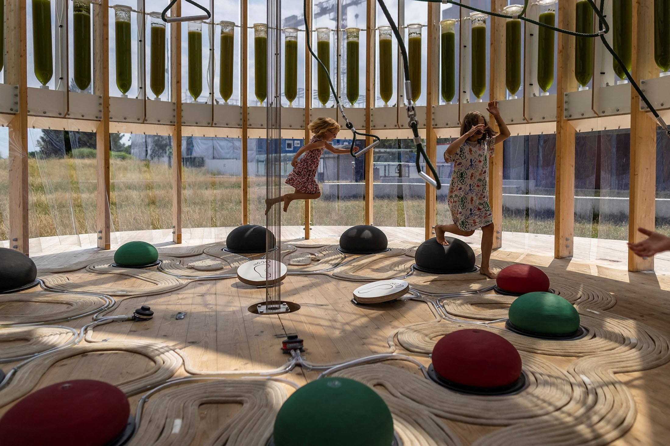 Six-year-old Janka and her friend nine-year-old Anielka play in an AirBubble, an innovative playground providing clean air thanks to algae that absorbs pollutants and CO2, in Warsaw, Poland, July 26, 2021. (AFP Photo)
