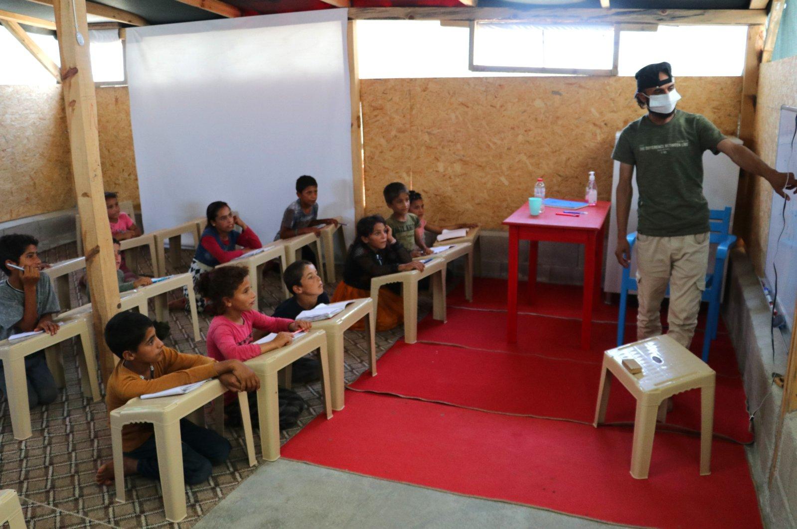 Ahmed Muhemid teaches his students inside the classroom, in Adana, southern Turkey, July 27, 2021. (IHA PHOTO)