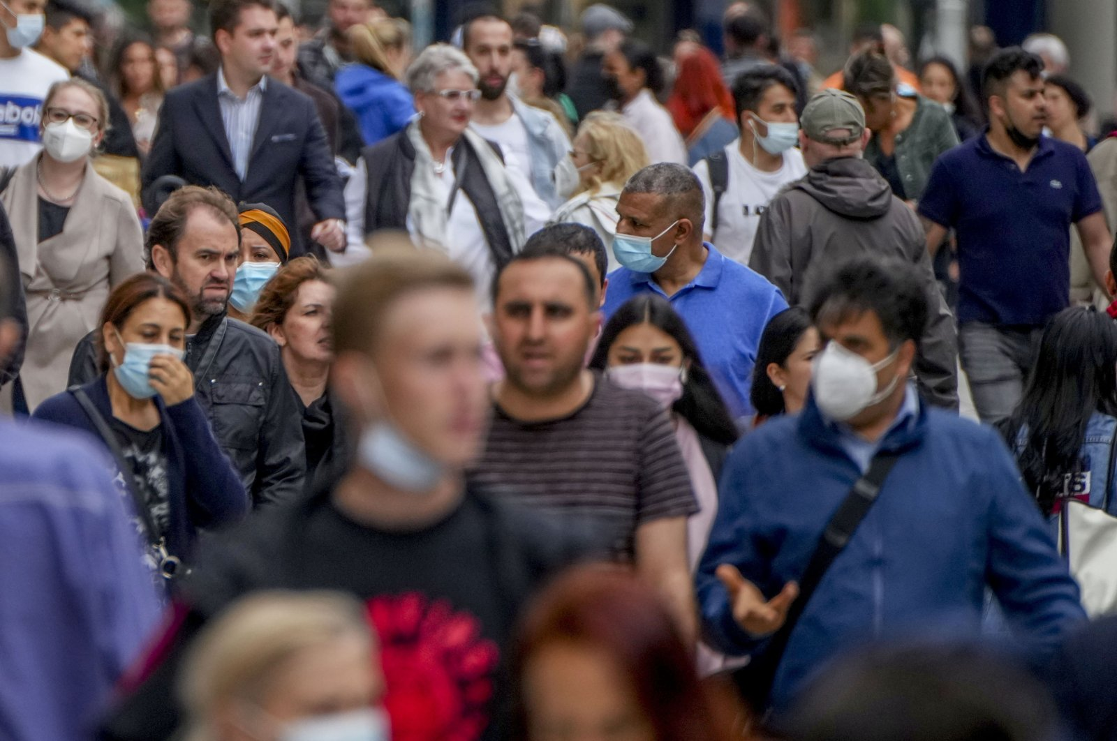 People, some with face masks and some without, walk on the main shopping street in Frankfurt, Germany, July 14, 2021. (AP Photo)