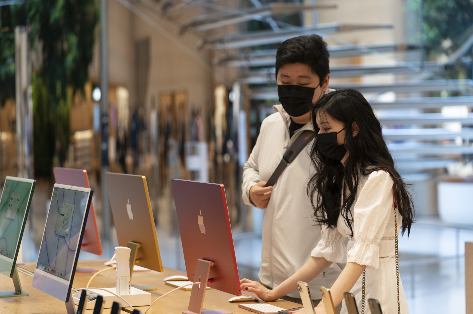 """Customers view the new 24"""" iMac desktop computers in an Apple store, in New York, U.S., May 21, 2021. (AP Photo)"""