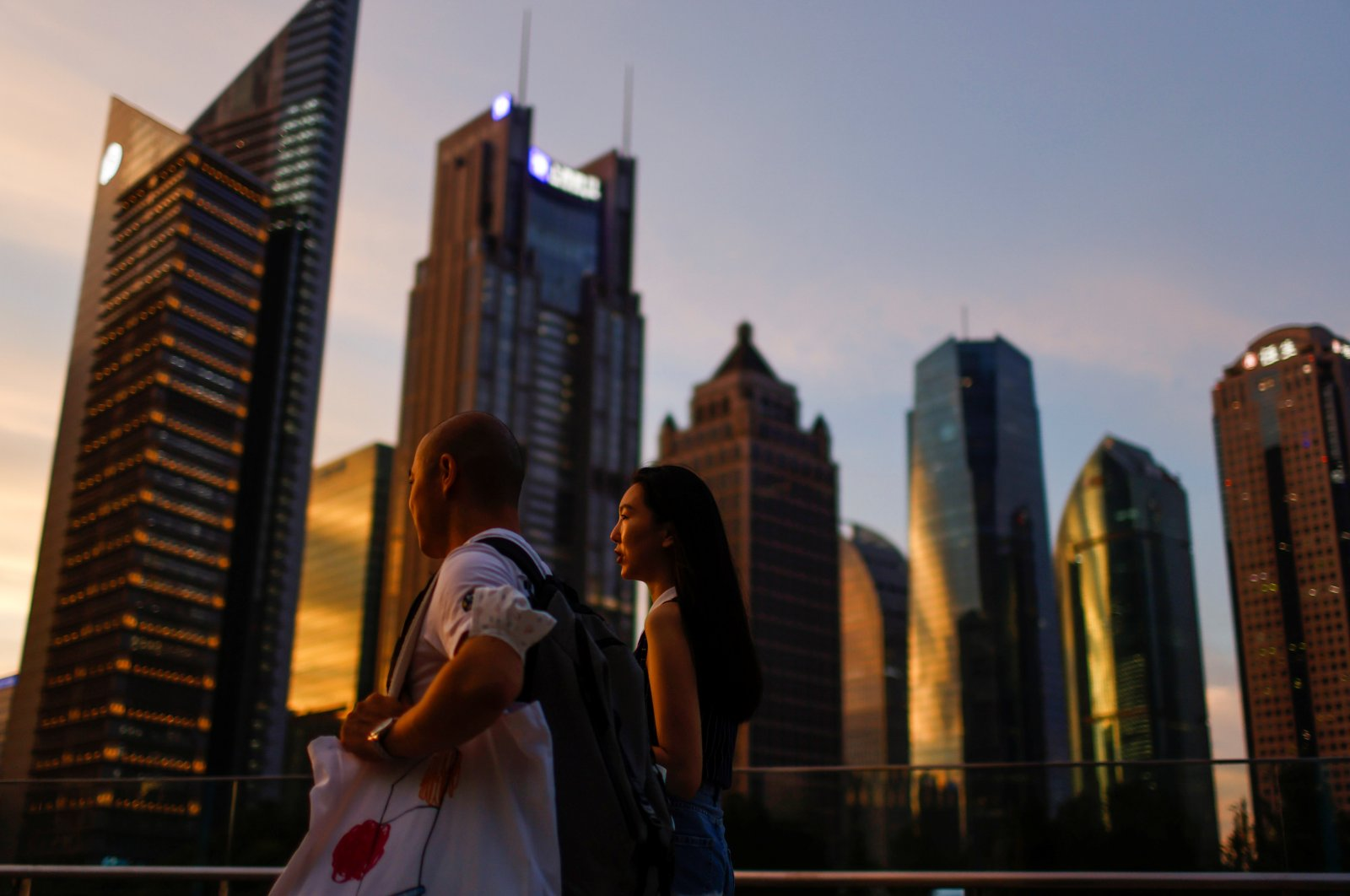 People walk in Lujiazui financial district during sunset in Pudong, Shanghai, China, July 13, 2021. (Reuters Photo)