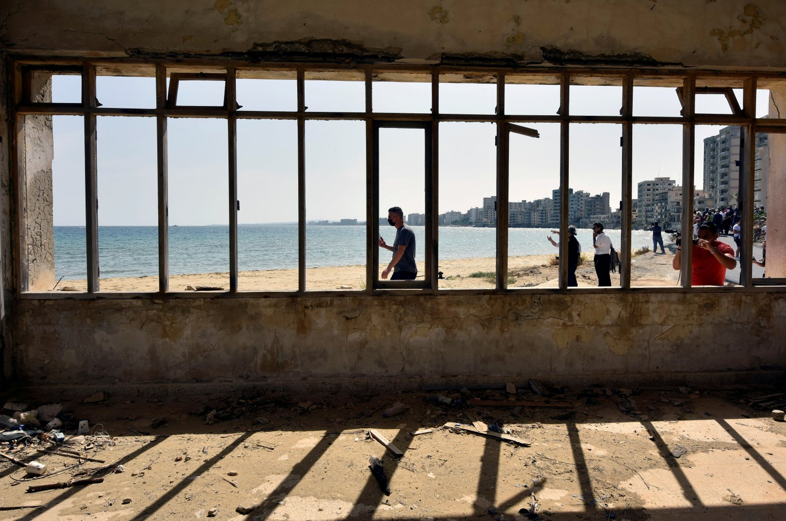 People walk on a beach inside an area fenced off by the Turkish military since 1974 in the abandoned coastal area of Varosha, a suburb of the town of Famagusta in the Turkish Republic of Northern Cyprus (TRNC), Oct. 8, 2020. (Reuters)