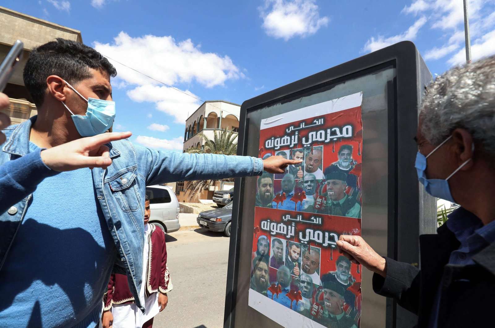 """Libyans look at a poster depicting members of a family who commanded a militia that traumatized Tarhuna town with the Arabic phrase """"al-Kani, Tarhuna's criminals"""", during a funeral procession for 12 bodies that were identified from mass graves found in Tarhuna town, March 26, 2021. (AFP)"""