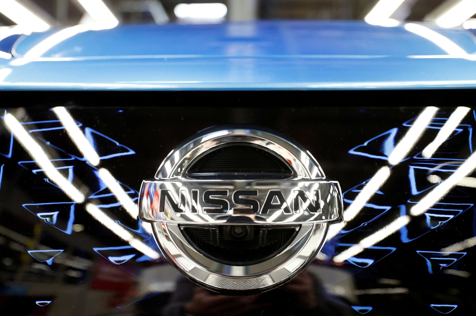 The logo of Nissan is seen on a car ahead of a news conference at Nissan's Sunderland plant in Sunderland, U.K., July 1, 2021. (Reuters Photo)