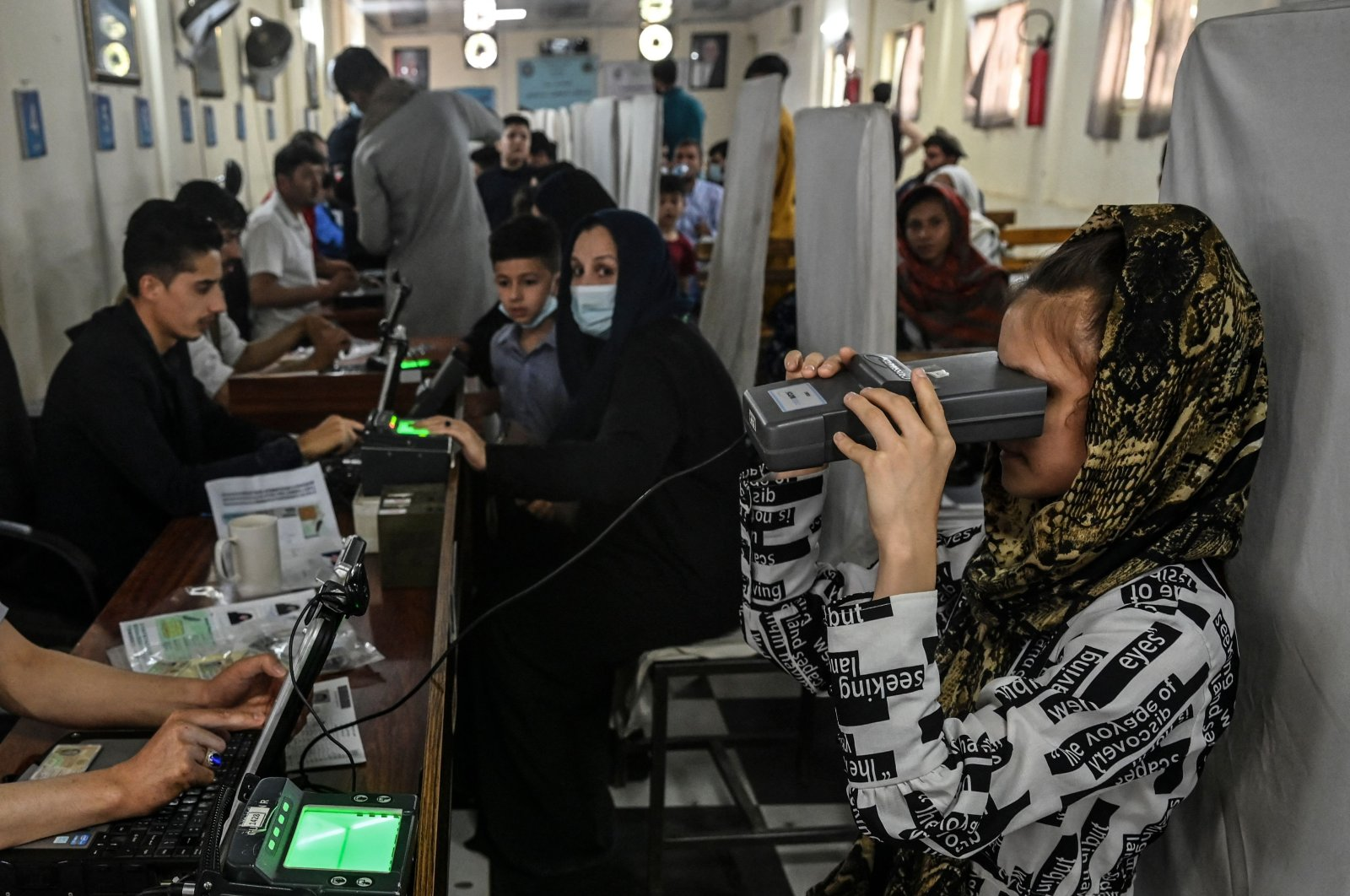 A woman looks through an optical biometric reader to submit her passport application at an office in Kabul, Afghanistan, July 25, 2021. (AFP Photo)