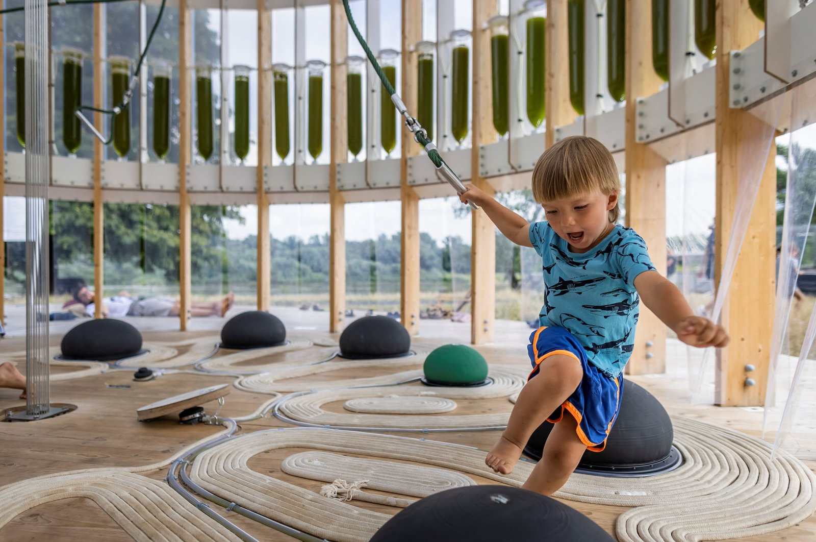 Four-year-old Felek plays in an AirBubble, an innovative playground providing clean air thanks to algae (seen in tubes in the background) that absorbs pollutants and CO2, in Warsaw, Poland, July 26, 2021. (AFP Photo)