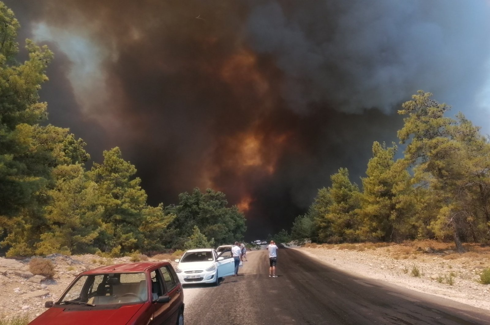 People watch as flames and a massive cloud of smoke cover a fire-hit area in Manavgat, Antalya, southern Turkey, July 28, 2021. (İHA PHOTO)