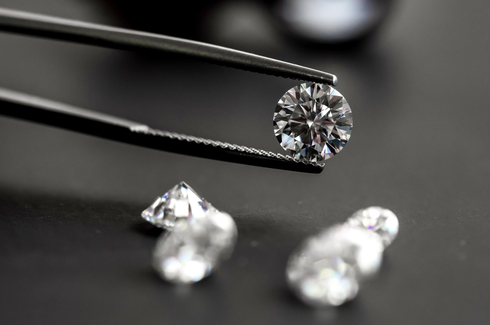 A diamond sparkles as it's held up in tweezers. (Shutterstock Photo)