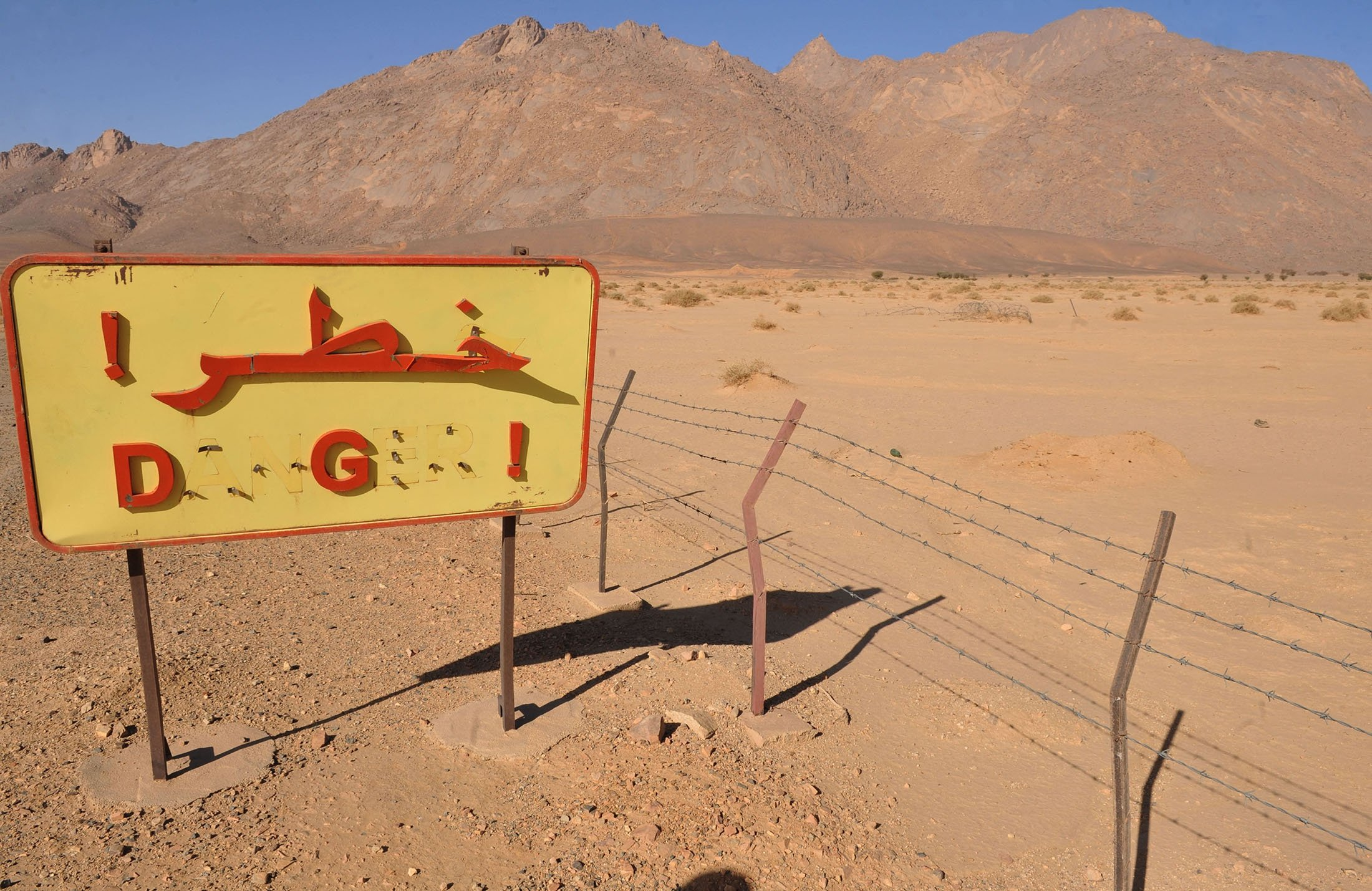 A defaced danger sign in Arabic and French, stands next to a fence at the entrance of the former French nuclear bomb test site of Tena Fila mountain at Ain Ekra in Tamanrasset, 2,000 kilometers (1,242 miles) south of Algiers, Algeria, Feb. 25, 2010. (AFP Photo)