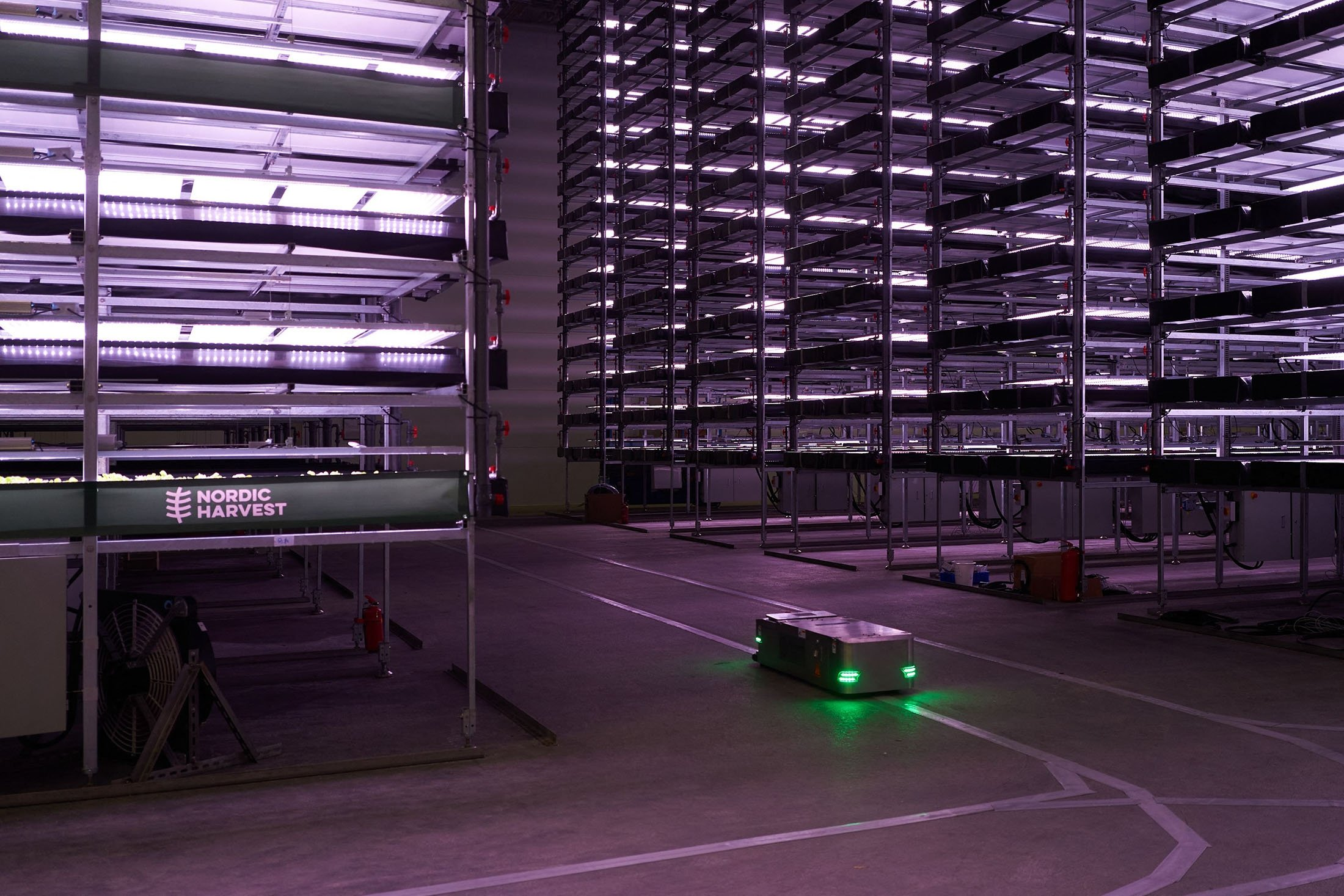 """A robot, used to plant seeds and check the plants while growing, moves past vertical racks at the vertical plant farm """"Nordic Harvest"""" based in Taastrup, a suburb west of Copenhagen, Denmark, Nov. 20, 2020. (AFP Photo)"""