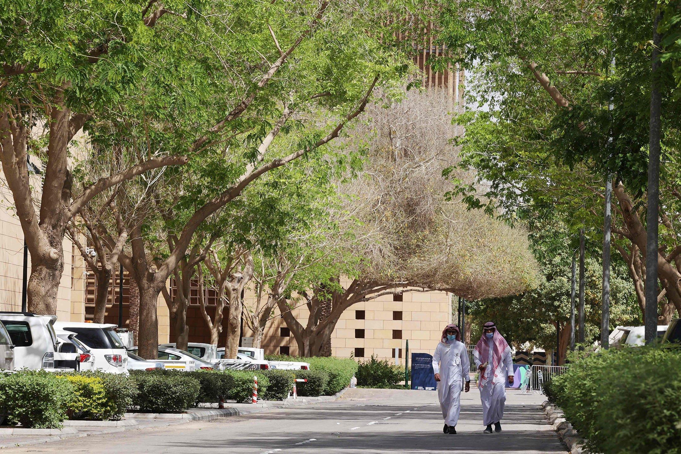 People walk on a tree-lined lane in the Saudi capital Riyadh, Saudi Arabia, March 29, 2021. (AFP Photo)