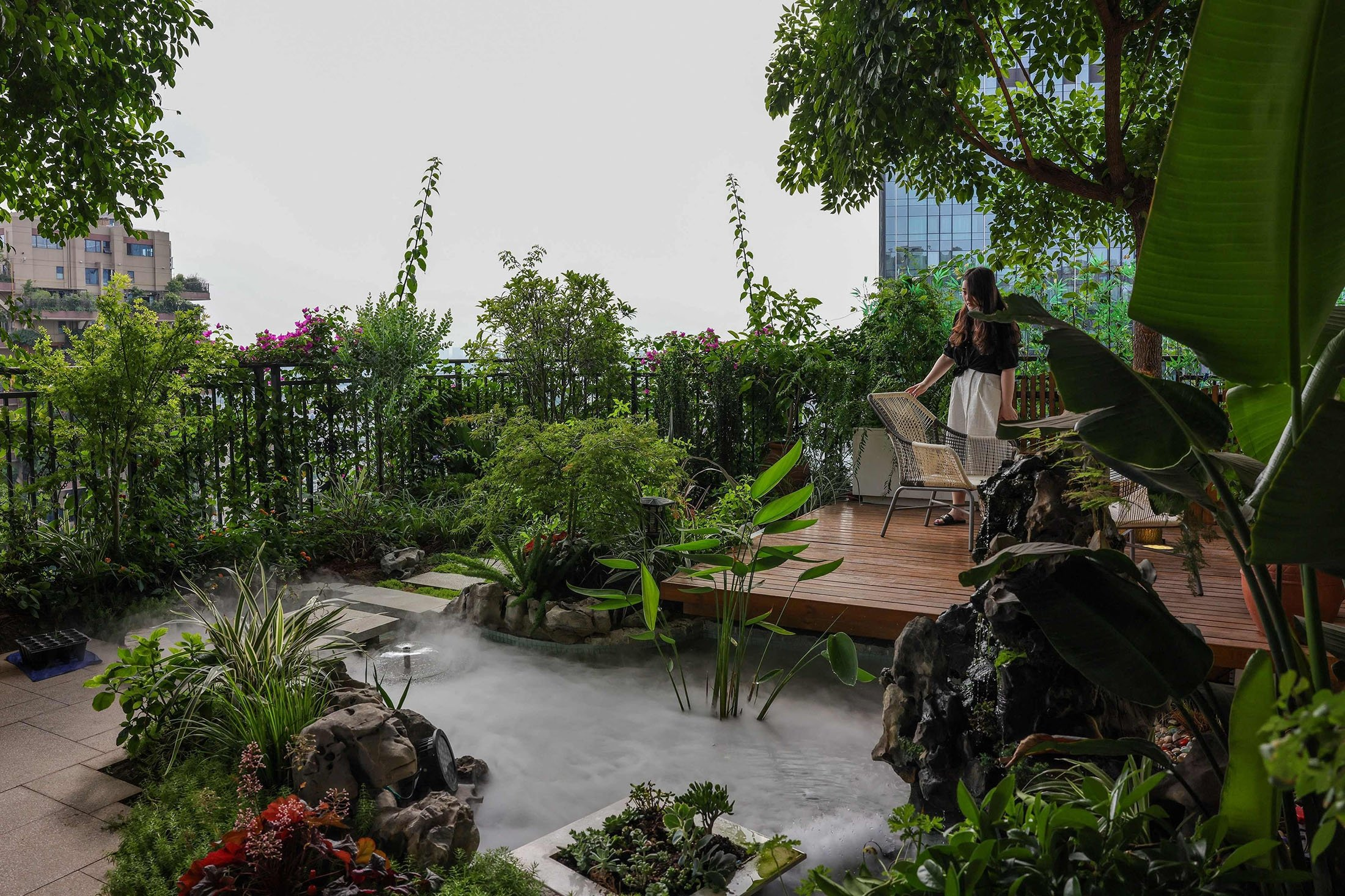 A woman rests on a balcony covered with plants at a residential community in Chengdu in China's southwestern Sichuan province, China, July 12, 2021. (AFP Photo)