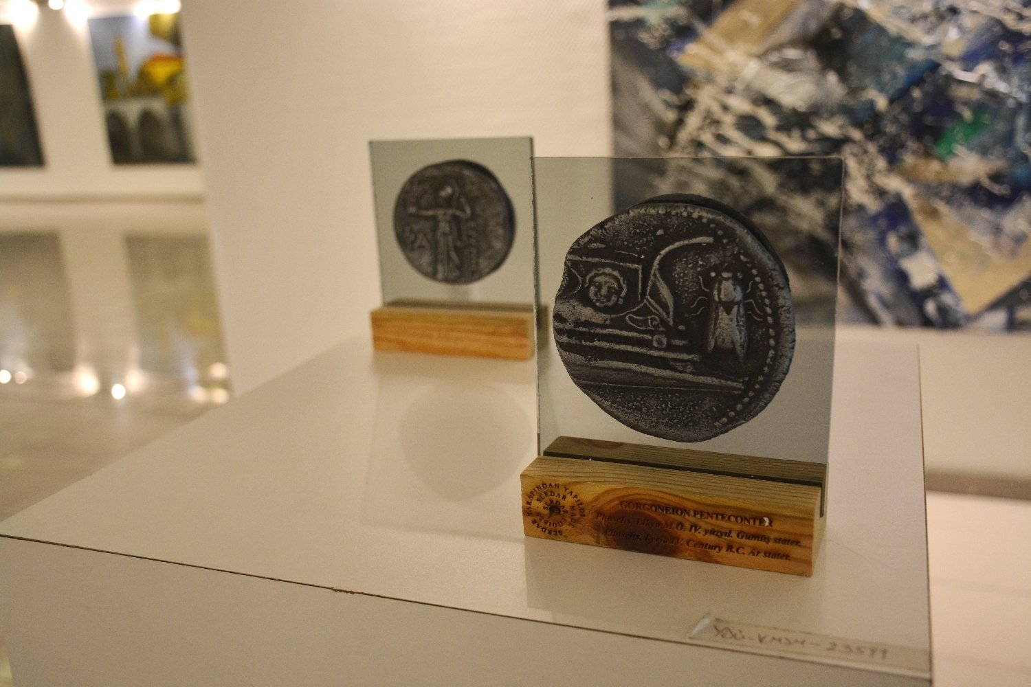 """Coins depicting ancient Lycian galleys from the """"Lycian Penteconters and Apollon Ceramics Exhibition after a 2000-Year Journey,"""" Cyprus Museum of Modern Arts."""