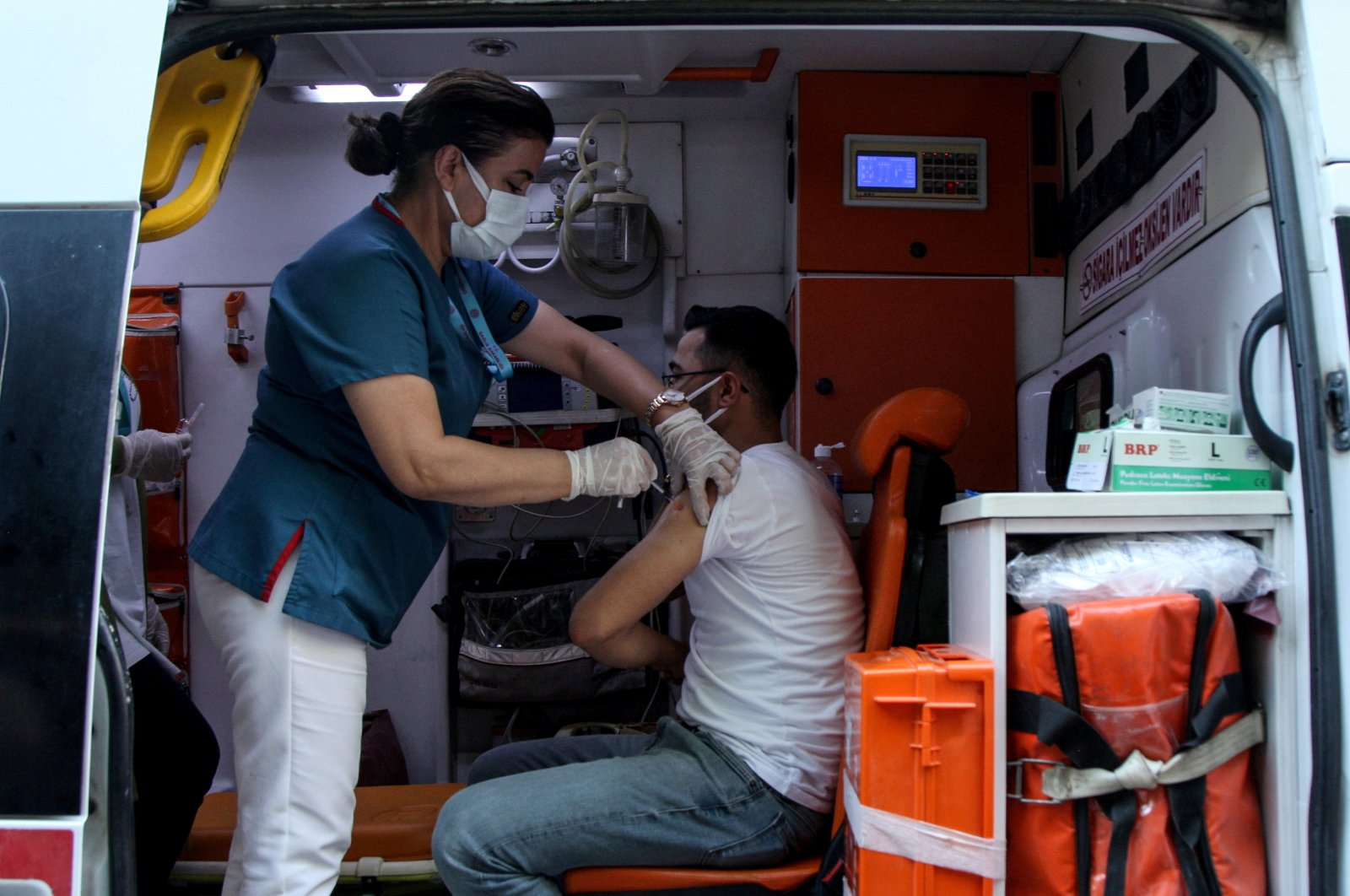 A man receives a dose of the Pfizer-BioNTech vaccine in an ambulance parked on a main street in Diyarbakır, southeastern Turkey, July 27, 2021. (REUTERS PHOTO)