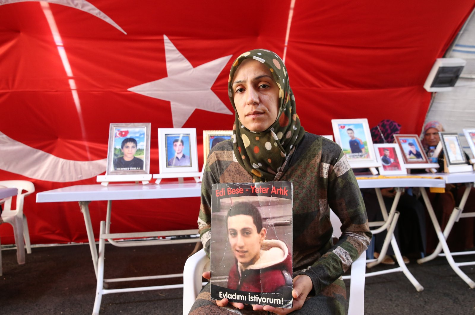 Mother Ayşegül Biçer holds a picture of her son, Mustafa, in front of the HDP headquarters in Turkey's Diyarbakır province, July 27, 2021. (AA Photo)
