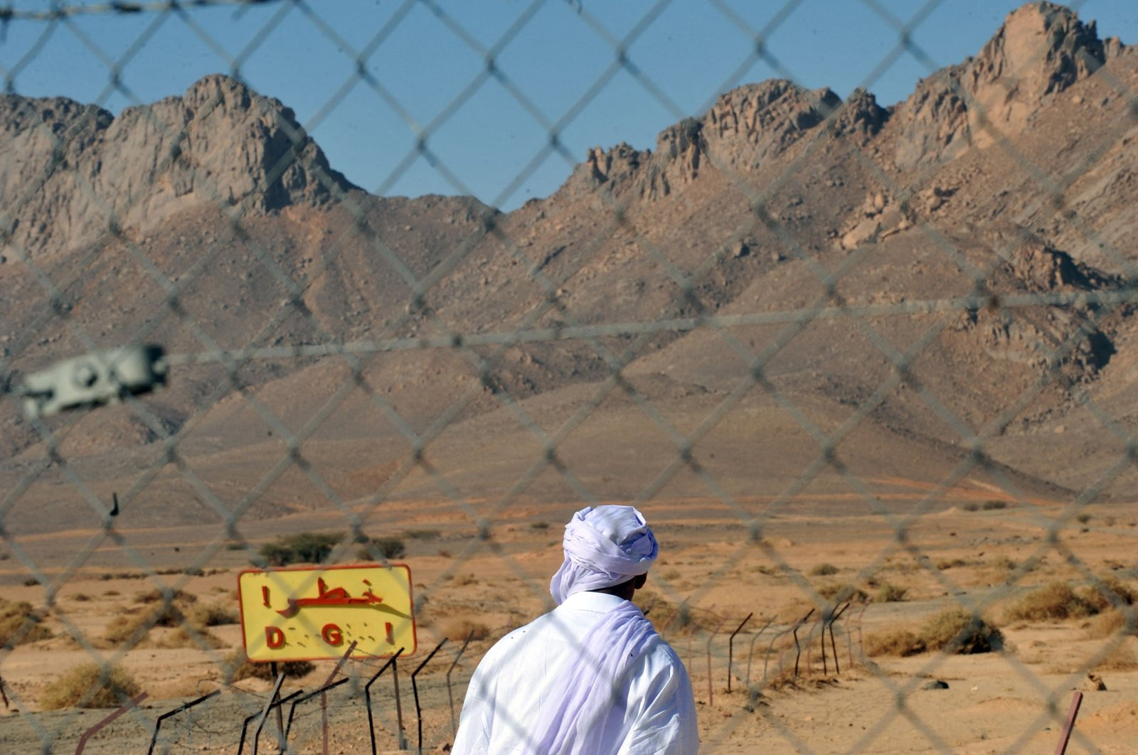 A man walks past a fence at the entrance of the former French nuclear bomb test site of Tena Fila mountain at Ain Ekra in Tamanrasset, 2,000 kilometers (1,242 miles) south of Algiers, Algeria, Feb. 25, 2010. (AFP Photo)