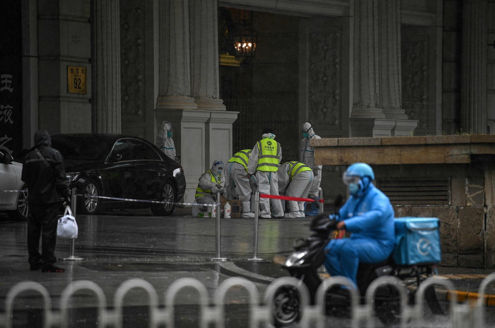 Health workers wearing personal protective equipment (PPE) stand at the entrance to the Legendale Hotel in the Wangfujing shopping district after China reported virus outbreaks in three cities, including the capital, Beijing, July 29, 2021. (AFP Photo)