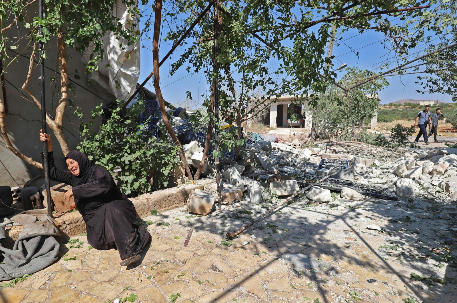 A Syrian woman reacts near the ruins of a house, destroyed in a reported regime artillery shelling, in the village of Iblin in the Jabal al-Zawiya region of Syria's opposition-held northwestern Idlib province, July 22, 2021. (AFP Photo)