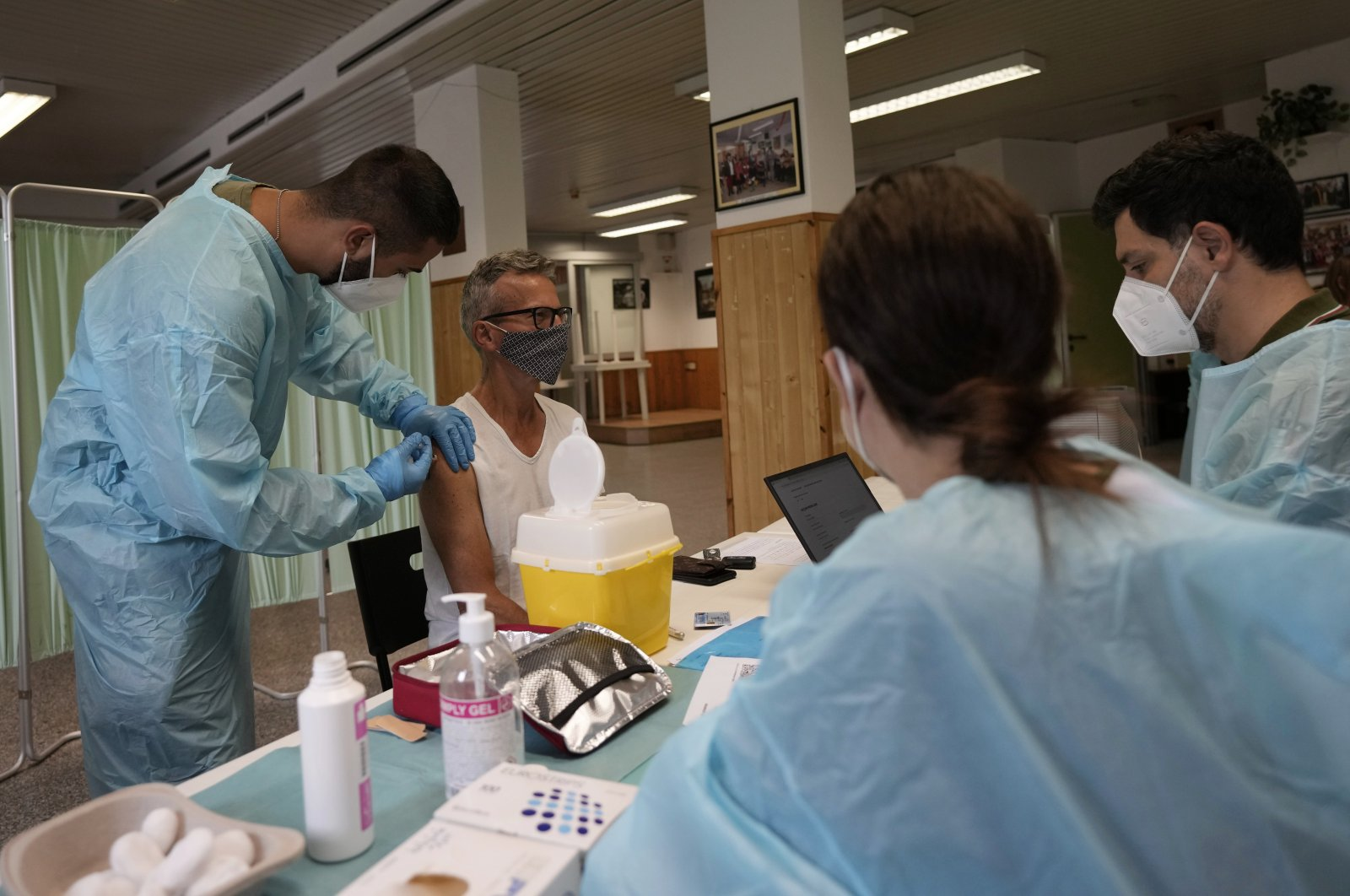 Medical workers administer the Johnson & Johnson vaccine for COVID-19 to Carlo Picella at a cultural center on the outskirts of Milan, Italy, July 28, 2021. (AP Photo)