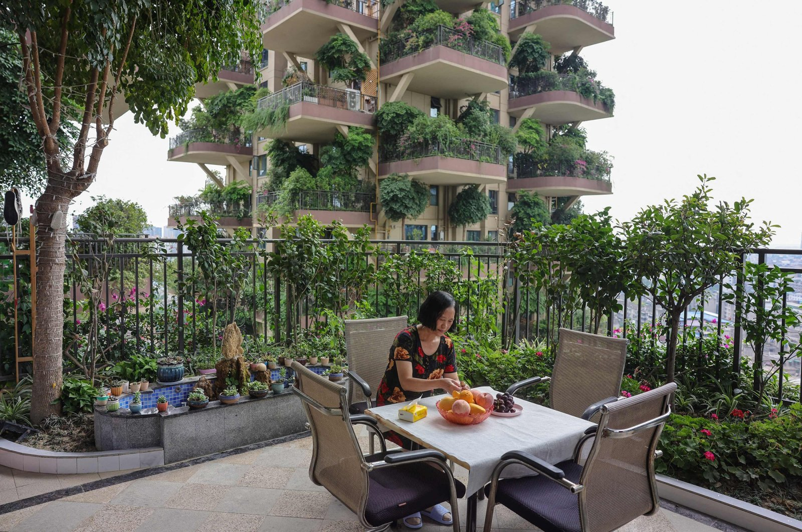 A woman sits on a balcony covered with plants at a residential community in Chengdu in China's southwestern Sichuan province, July 12, 2021. (AFP Photo)