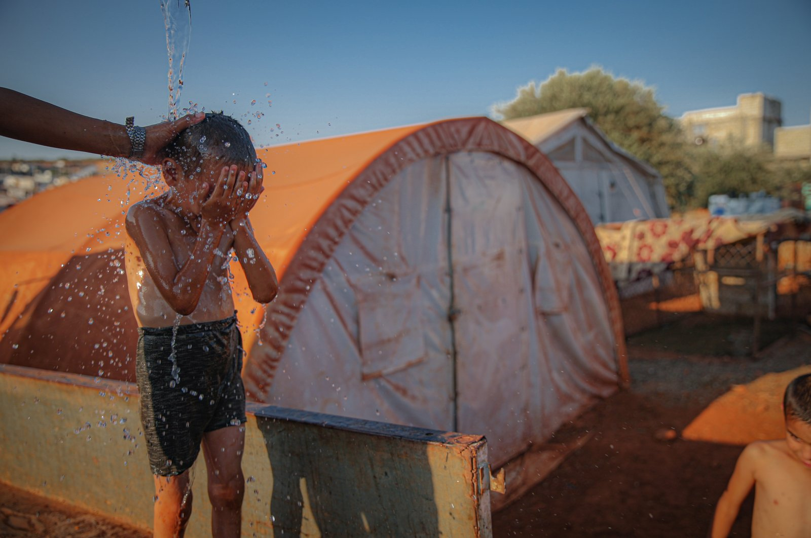 A child is seen near their tent in a camp for displaced people in Idlib, northwestern Syria, July 29, 2021. (AA Photo)