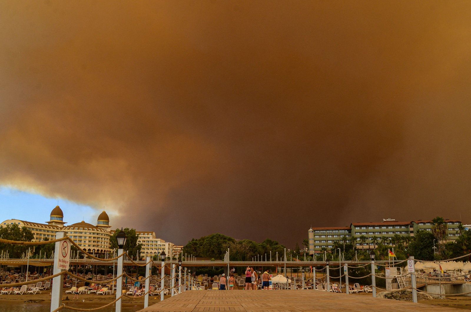 Dark smoke drifts over a hotel complex during a massive forest fire that engulfed a Mediterranean resort region on the southern coast near the town of Manavgat, Antalya, southern Turkey, July 29, 2021. (AFP Photo)