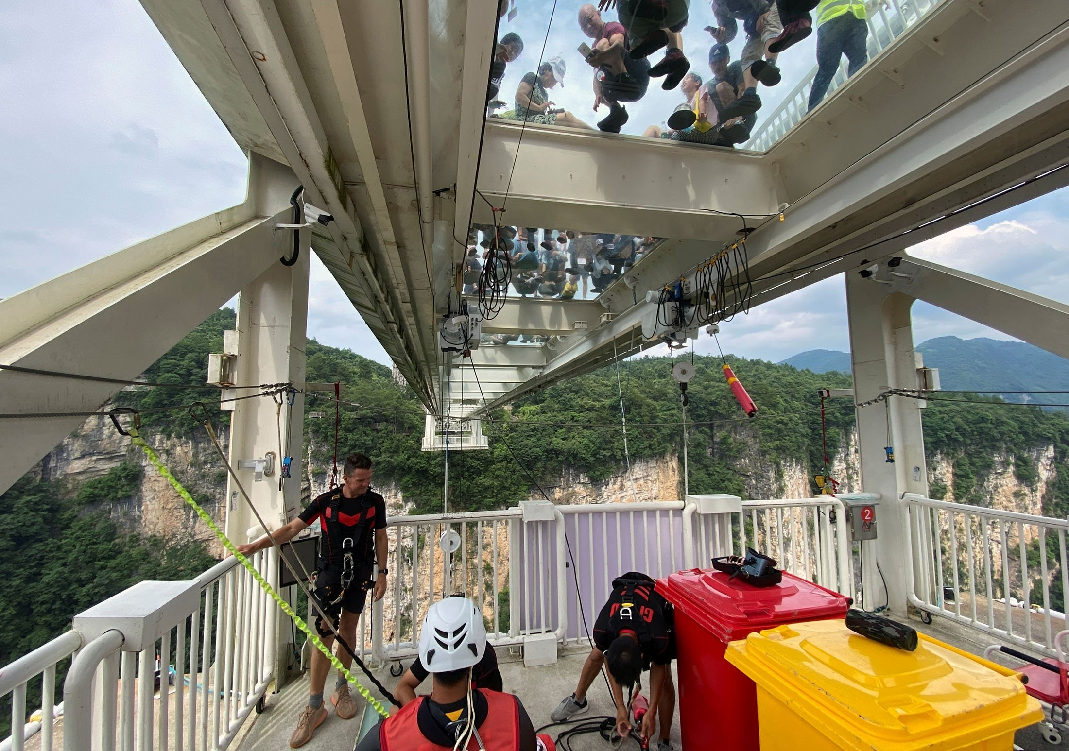 Visitors peek through a 430-meter (1,410-foot) long glass-bottomed bridge as Jonni Deaker, site manager for Beau Ratalic Bungy Jumping, helps a participant to get ready for a bungee jump from a 260-meter high platform over the Zhangjiajie Grand Canyon in Zhangjiajie, Hunan province, China, July 11, 2021. (Reuters Photo)