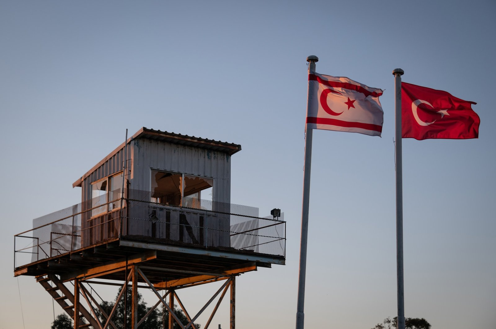 Turkish and Turkish Cypriot flags wave in the wind near an abandoned observation tower on the green line in Nicosia, (Lefkoşa), TRNC, April 21, 2019. (Getty Images)