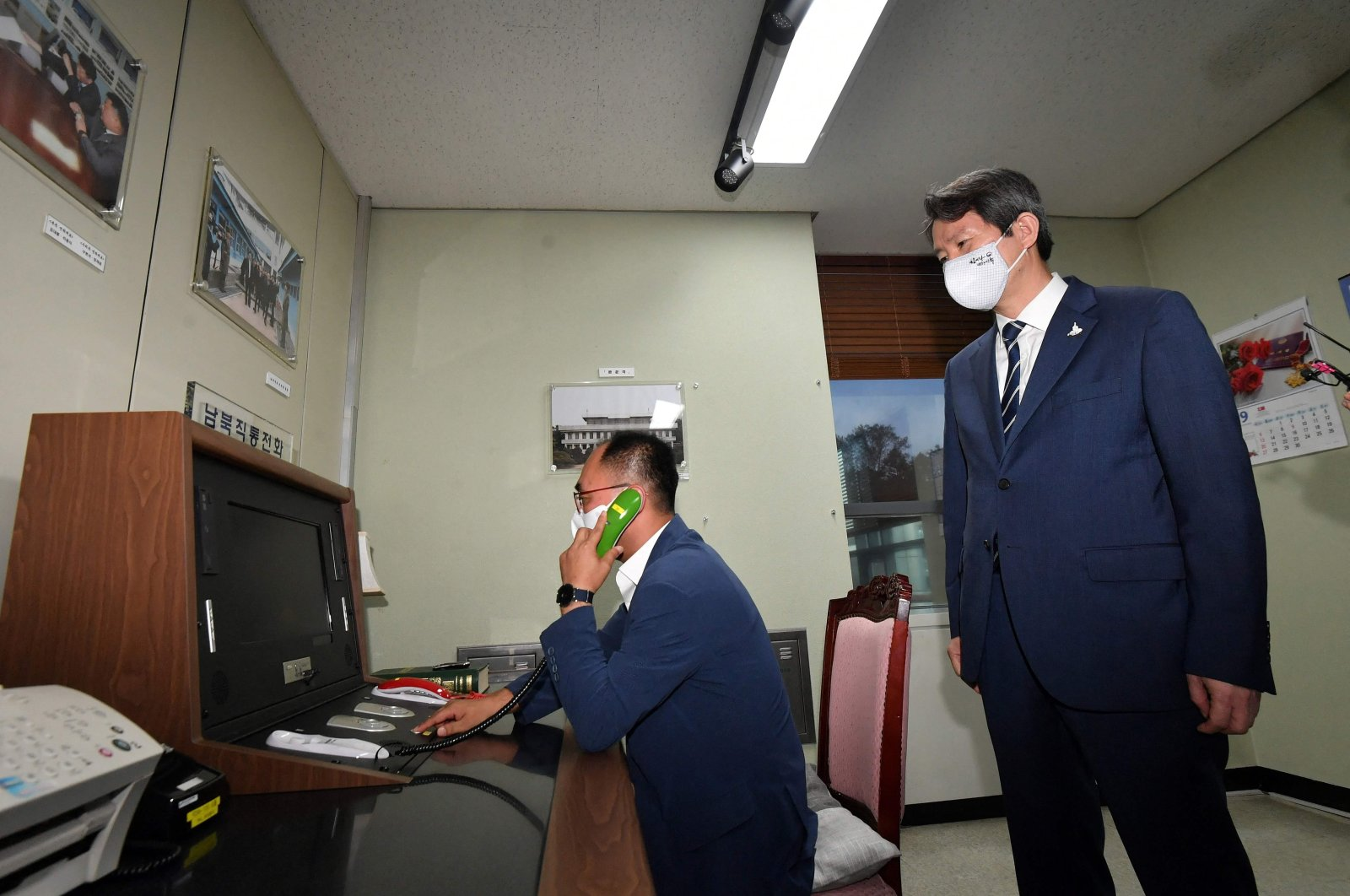 """South Korea's Unification Minister Lee In-young (R) looking at the inter-Korean """"hotline"""" during a visit to the south side of the truce village of Panmunjom in the Demilitarized Zone (DMZ) dividing the two Koreas, Sept. 16, 2020. (AFP Photo)"""