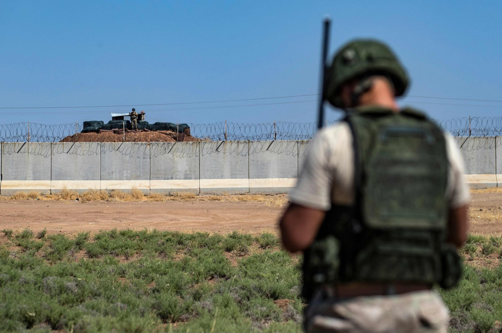 A Russian soldier is pictured as a Turkish soldier stands behind the border with Syria, during a joint Turkish and Russian patrol of military vehicles (unseen) in the countryside of the town of Derbassiye in Syria's northeastern Hasakeh province, on the border with Turkey, July 14, 2021. (AFP Photo)