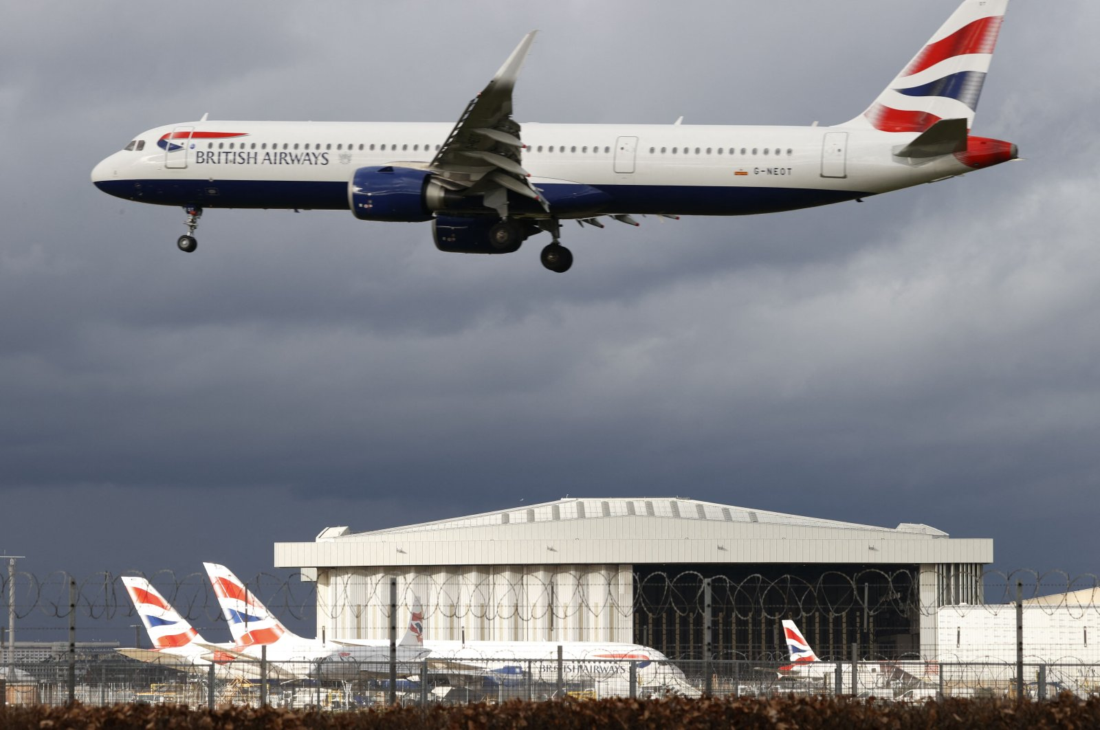 A British Airways aircraft flies over parked British Airways planes on the tarmac at London Heathrow Airport in west London, U.K., Feb. 5, 2021. (AFP Photo)