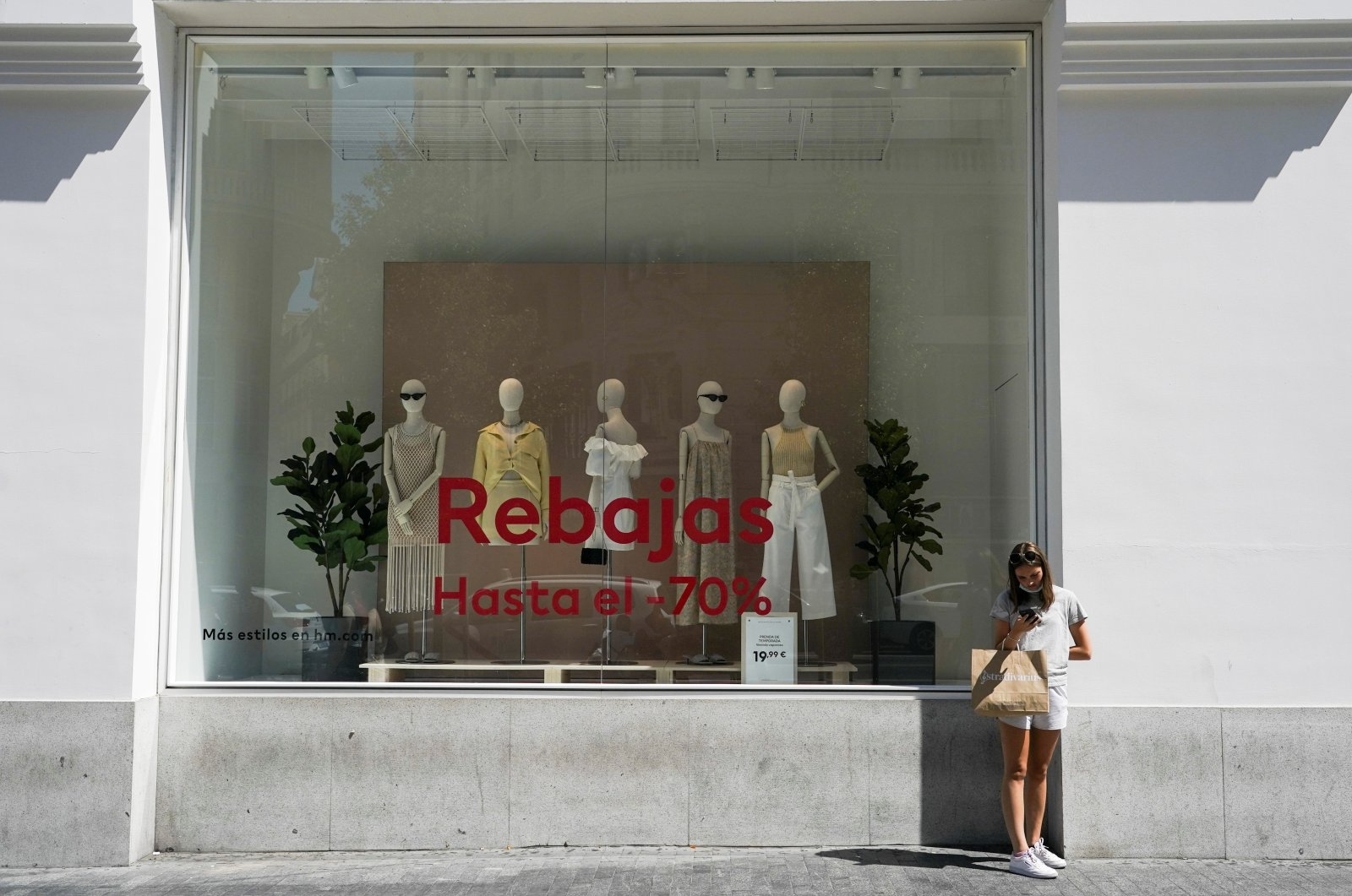 A woman with a shopping bag stands outside a shop at a commercial district in Madrid, Spain, July 27, 2021. (Reuters Photo)