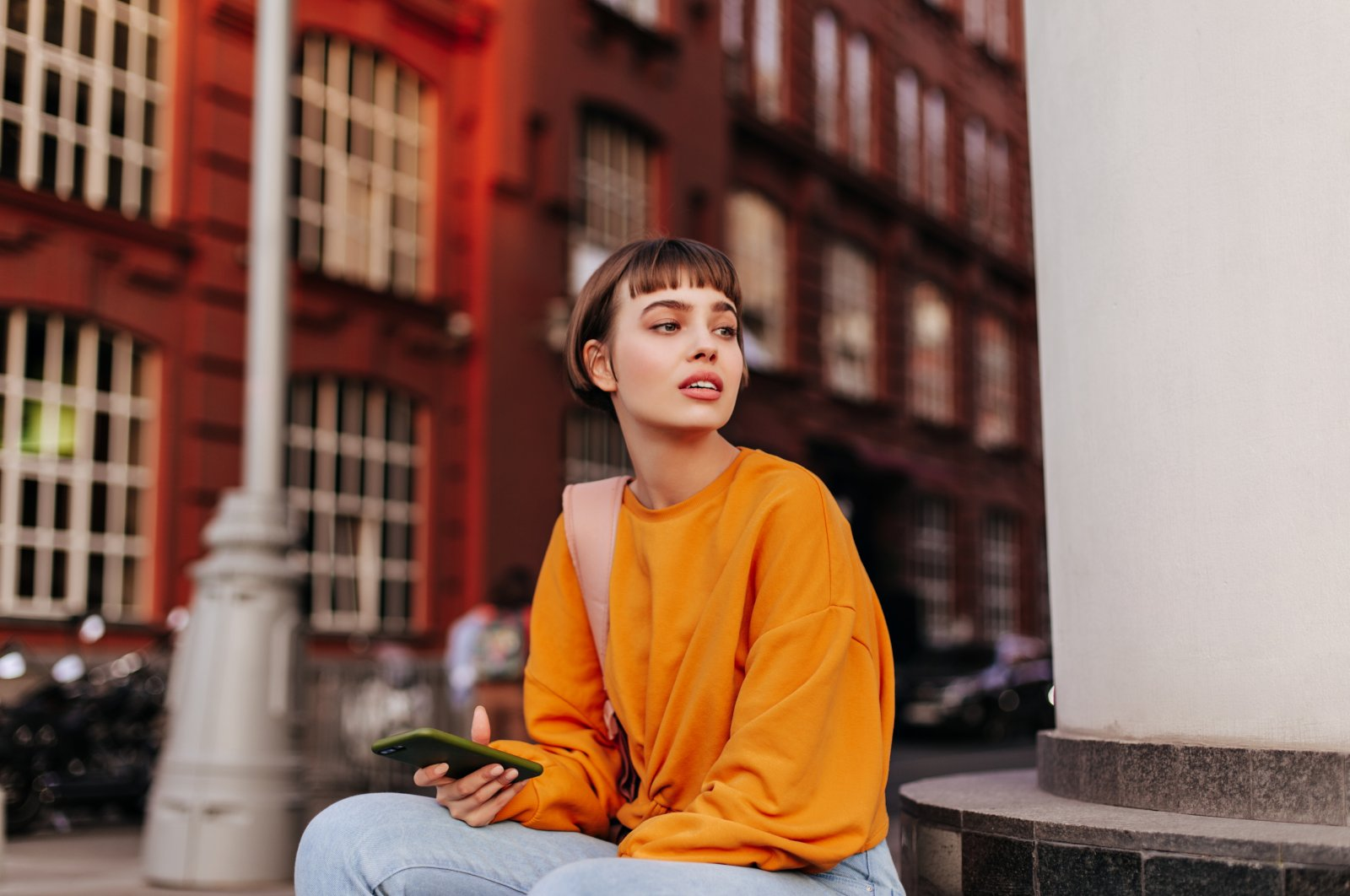 Cheerful young girl in an orange sweatshirt and jeans walks outdoors. (Shutterstock Photo)
